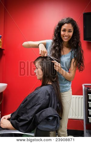 Portrait of a happy female hairdresser cutting hair with scissors