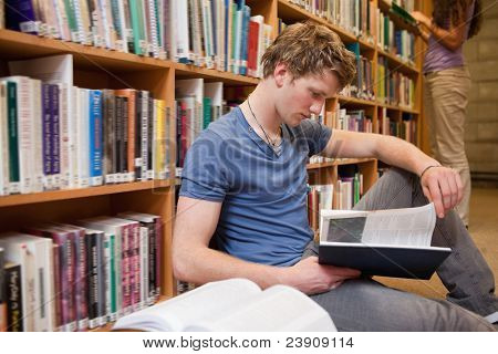 Male student reading a book in a library