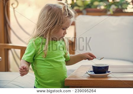 Childhood And Baby Care Concept. Boy Child Mixing Sugar In Blue Cup. Little Kid Boy Making Tea. Chil