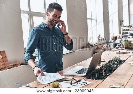 Taking Care Of Business. Handsome Young Man Talking On Smart Phone And Smiling While Working In The