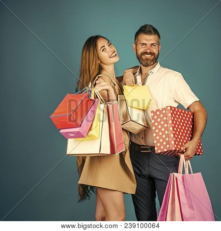Couple In Love Hold Shopping Bag Near Blue Wall. Shopping And Sale. Black Friday, Happy Holiday, Rel