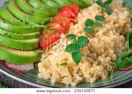 Porridge Bulgur With Salad Avocado, Tomatoes And Arugula. Rustic Concrete Background. Top View.
