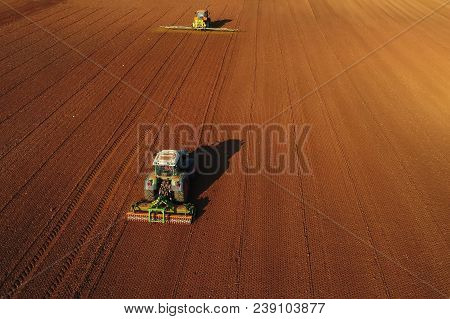 Aerial Shot Of  Farmer With A Tractor On The Agricultural Field Sowing.