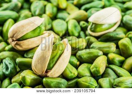 Green pistachio nuts with shell over lot of pistachios. Food background.