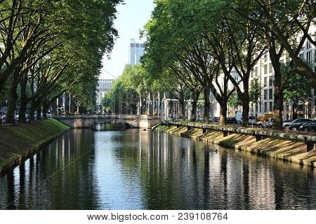 Dusseldorf, Germany - July 8, 2013: People Walk Along Famous Konigsallee Boulevard In Dusseldorf. Ko