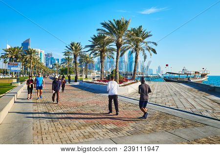 Doha, Qatar - February 13, 2018: Scenic Park With Lush Palms And Bright Flower Beds Stretches Along