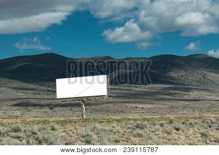 Blank Billboard For Advertising Mounted On A Meadow Among The Mountains, Blank White Billboard Again