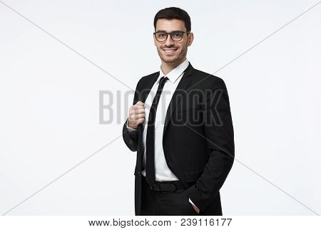 Half-length Portrait Of Handsome Caucasian Guy Dressed In Black Suit, White Shirt And Tie Isolated O