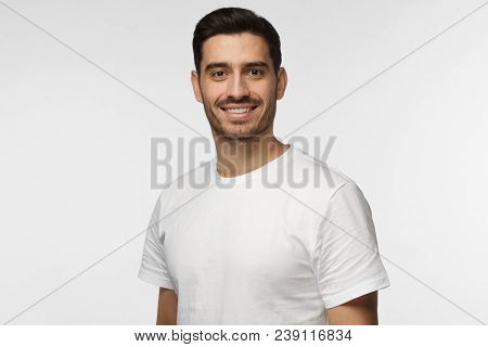 Indoor Closeup Of Young Good-looking European Man Isolated On Gray Background Dressed In White T-shi