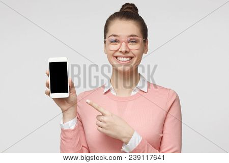 Closeup Picture Of Young European Caucasian Lady Pictured Isolated On Grey Background Holding Blank