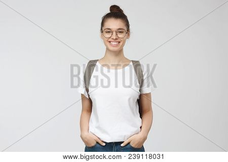 Indoor Picture Of Young Good-looking Teenage Girl Isolated On Gray Background In White Casual T-shir