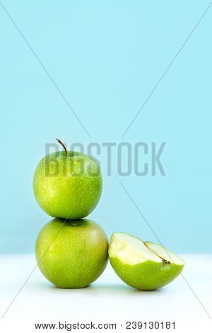 One Green Tasty Apple On Another And Next Half Bitten Apple On Blue Background