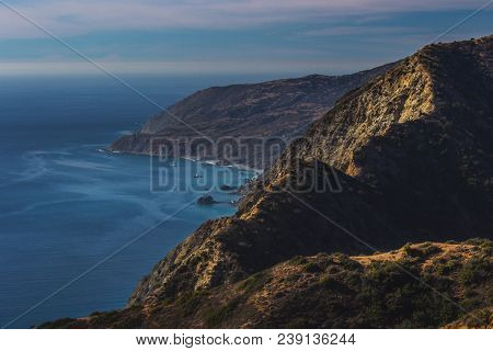 Stunning Mountaintop View Of Rugged Catalina Coastline And Canyons On A Sunny Day With Clouds In The