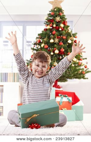 Happy kid sitting in pyjama on christmas morning, raising arms, getting christmas gift, laughing at camera.?