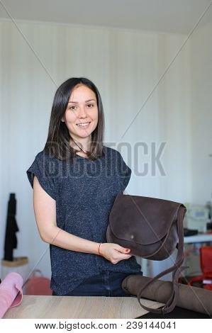 Pretty craftswoman standing with brown leather handmade bag at atelier. Concept of hahdicraft and business. poster