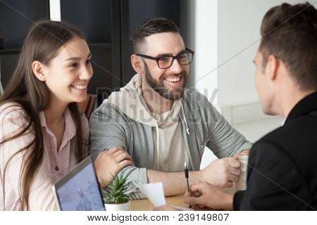 Excited Smiling Millennial Couple Discussing Mortgage Loan Investment Or Real Estate Purchase With R