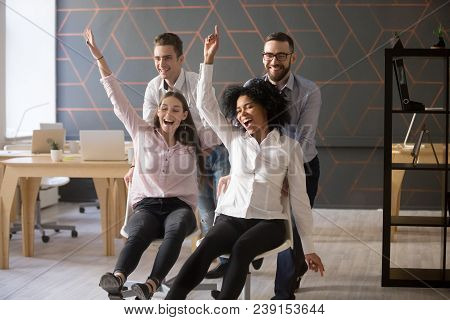 Excited Diverse Colleagues Having Fun Riding Oh Chairs In Office, Happy Coworkers Employees Enjoying