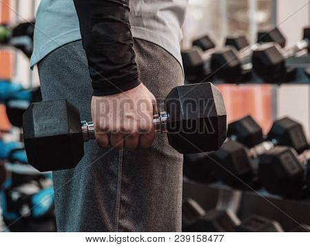 Powerful Bodybuilder Doing The Exercises With Dumbbells. Man Doing One-arm Row Exercise For His Back