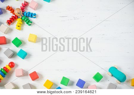 Kids Toys Frame Wooden Blocks, Octopus, Car, Pyramidion On White Wooden Background. Top View. Flat L