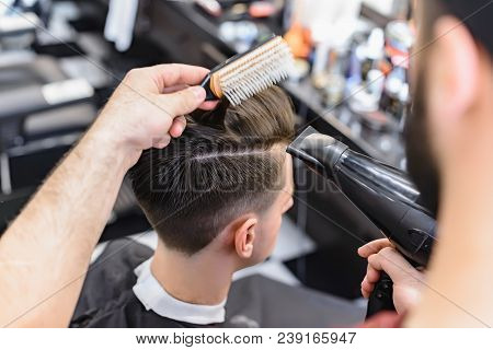 Professional Barber Styling Hair Of His Client. Barber Makes Hair Styling With A Hair Dryer.