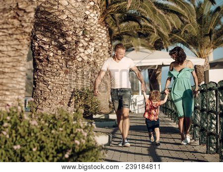 Mother And Father With Son Walk At Beach Palms. Summer Vacation Of Happy Family. Love And Trust As F