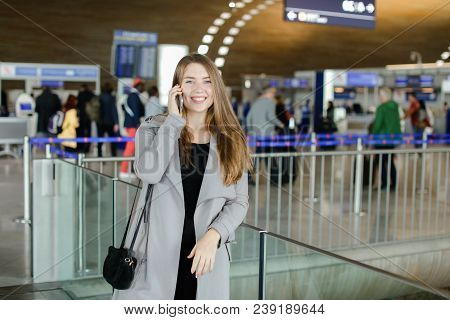 Girl Talking By Smartphone At Airport Hall, Wearing Grey Coat And Black Bag. Concept Of Speaking Wit