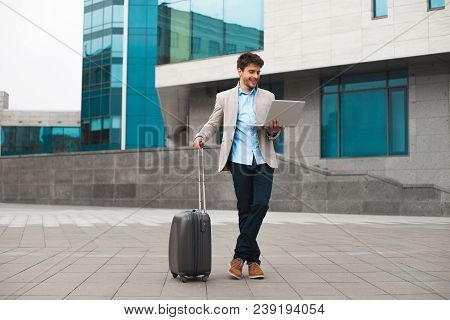 Going Forward! Smiling Awesome Businessman Holding A Laptop And Standing With Baggage At The Airport