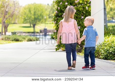 Young Sister and Brother Holding Hands And Walking At The Park.
