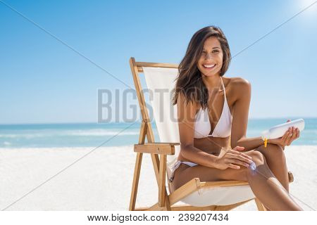 Young woman in bikini sitting on deckchair and applying sun lotion on leg. Portrait of smiling latin girl applying sun screen on body at beach with copy space. Beautiful woman enjoying sunbathing.