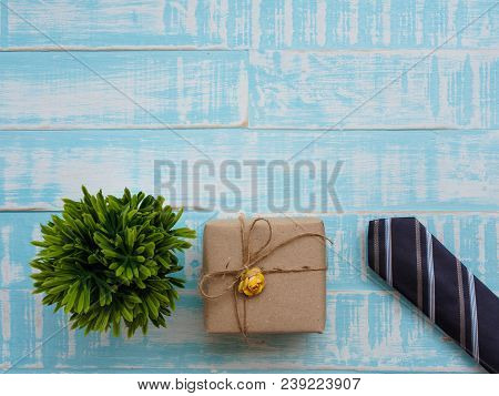 Happy Father's Day Inscription With Colorful Tie,gift Box And Plant On Bright Blue Wooden Background
