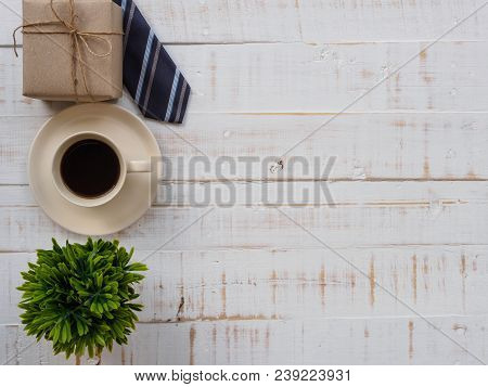 Happy Father's Day Inscription With Colorful Tie, Gift Box, Plant And A Cup Of Coffee  On White Wood