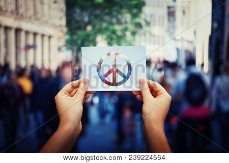 Close Up Of Woman Hands Holding A White Paper Sheet With Peace Symbol Over A Crowded City Street Bac