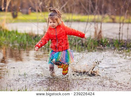 Little Smiling Girl In Spring Coat And Colorful Skirt With Gumboots Playing In Splashing Water Of Pu