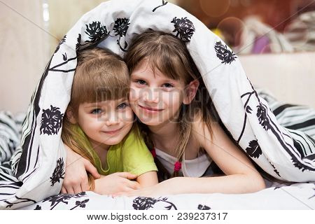 Funny Little Sisters Hides Under Blanket. Cute Girls Having Fun On Bed. Concept Of Kids Sleep, Care