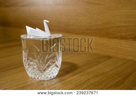Paper Crane On A Crystal Glass On A Wood Table Composition