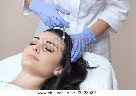 poster of Procedure of mesotherapy. The doctor cosmetologist makes the procedure of mesotherapy in woman's head. Strengthen hair and their growth.