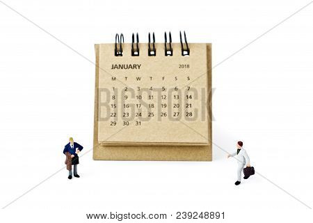 January. Meeting In January. Two Thousand Eighteen Year Calendar And Two Miniature Plastic Businessm