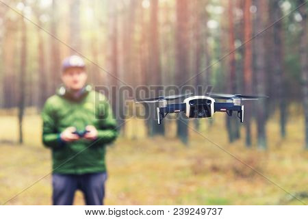 Man Flying Drone In The Woods. Focus On Drone