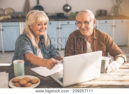 Portrait Of Happy Senior Married Couple Solving Issues By Internet At Home. Woman Is Dealing With Pa