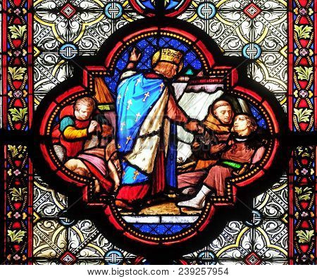 PARIS, FRANCE - JANUARY 05: Saint Louis attending the plague victims, stained glass window in the Basilica of Saint Clotilde in Paris, France on January 05, 2018.