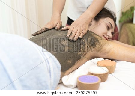 Beautiful Young Woman Getting A Mud Massage At Spa Salon, Health And Healing Concept.