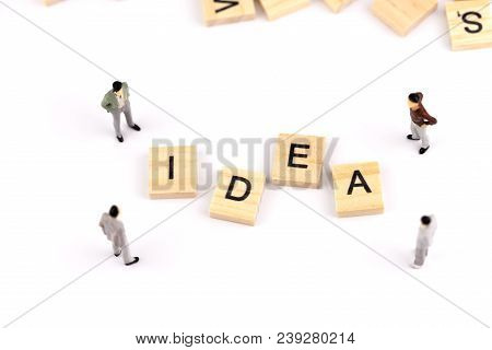 Business Idea Concept. Miniature People Small Figure Standing Around A Wooden Cube With Word Idea Is