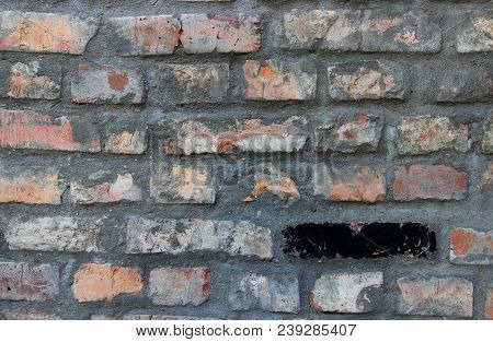 One Black Brick In The Old Worn Red Brick Wall. Grunge Texture Background.