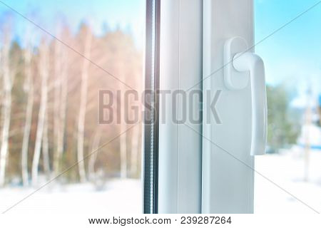 Plastic Window With Handle. Cold Winter Weather Outside The Window.