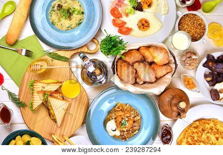 A Big Breakfast Feast On A White Wooden Table In A Sunny Morning. Buffet Breakfast In A Hotel.