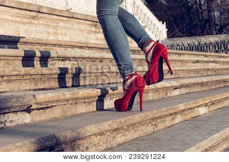 Woman Wearing Blue Jeans And Red High Heel Shoes In Old Town. The Women Wear High Heels Walk Up Stai