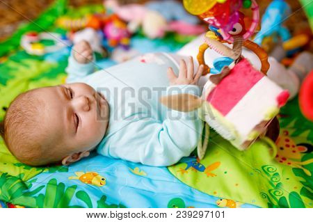 Cute Adorable Newborn Baby Playing On Colorful Toy Gym And Looking At The Camera. Closeup Of Peacefu