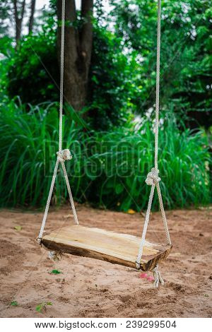 A Brown Wooden Swing In The Garden