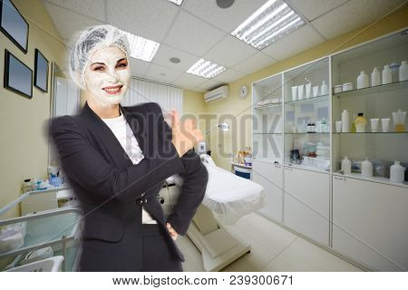 Collage with woman with cosmetic face mask in black business suit holding thumb up on background of room with cosmetic couch, equipment and various cosmetic preparations