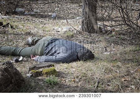 Murder In The Woods, A Dead Man In A Blue Sweater And Green Pants Lying On The Ground Among The Tree